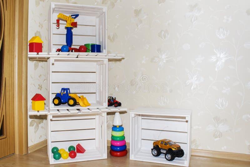 Jonge geitjesruimte, Behang en houten kratten in milieuvriendelijke planken voor speelgoed stock foto
