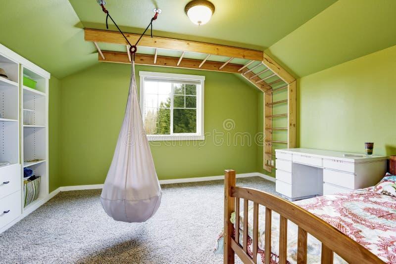 Jonge geitjesruimte in heldergroen met het hangen van stoel stock fotografie