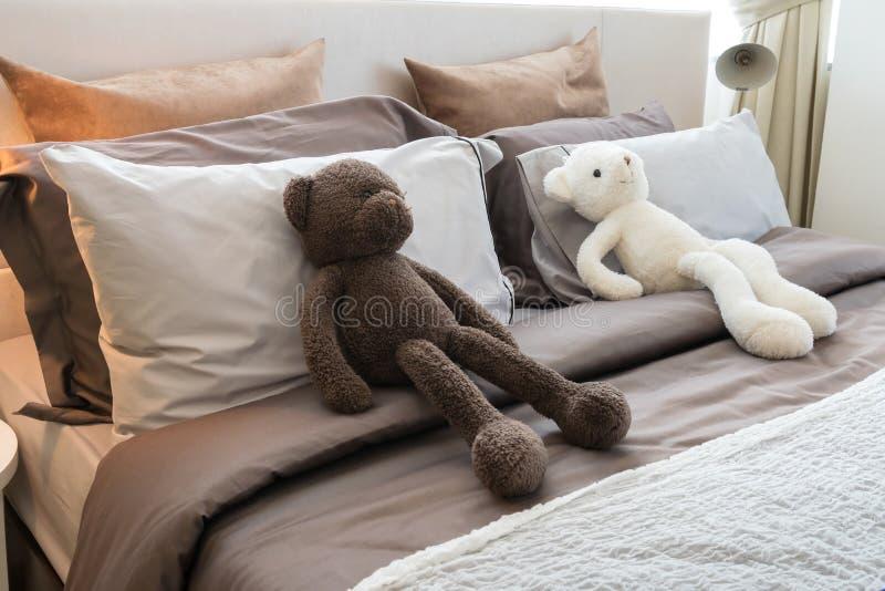 Jonge geitjesruimte met poppen en hoofdkussens op bed stock afbeeldingen