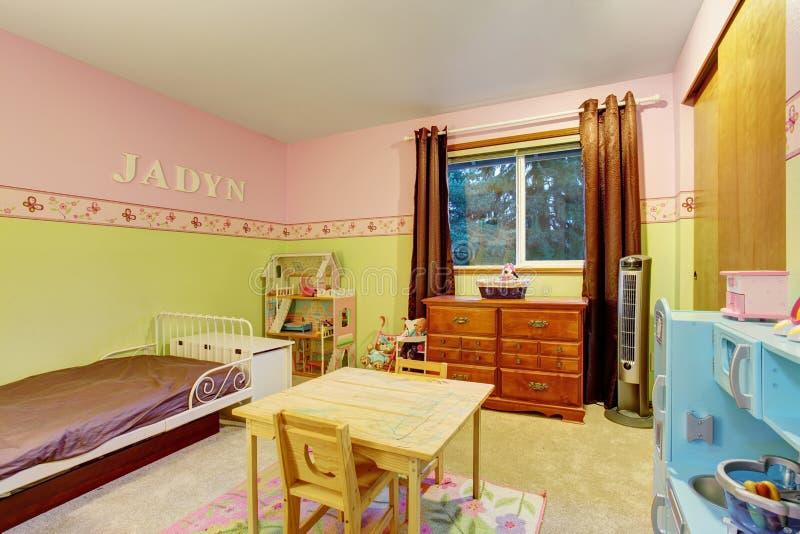 Jonge geitjesslaapkamer met roze en groene geschilderde muren royalty-vrije stock afbeelding