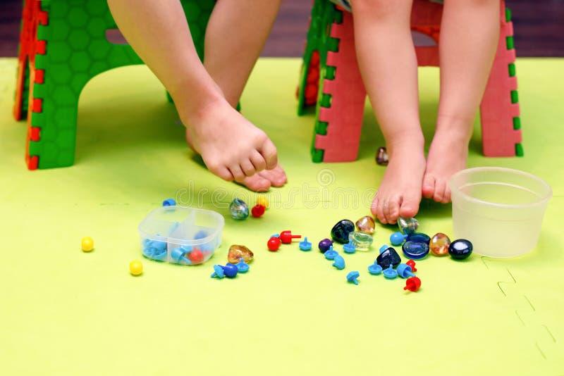 Jonge geitjesspel met mozaïekstukken, glasstenen Orthopedisch spel, gymnastiek met valgus, massage en stimulatie van de spieren v royalty-vrije stock afbeeldingen