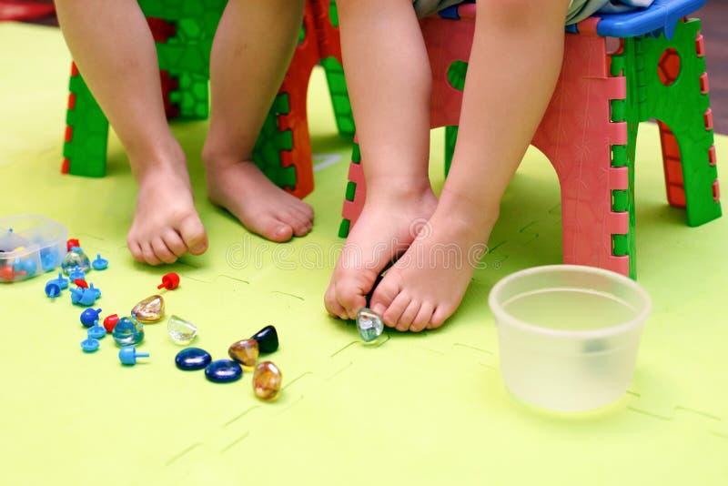 Jonge geitjesspel met mozaïekstukken, glasstenen Orthopedisch spel, gymnastiek met valgus, massage en stimulatie van de spieren v royalty-vrije stock foto