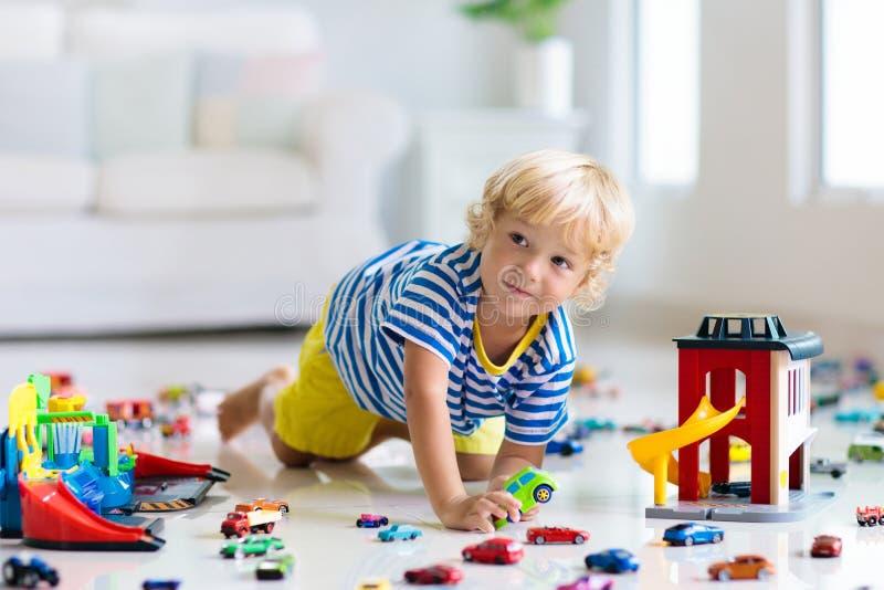 Jonge geitjesspel met stuk speelgoed auto's Kinderen die autospeelgoed spelen stock afbeelding