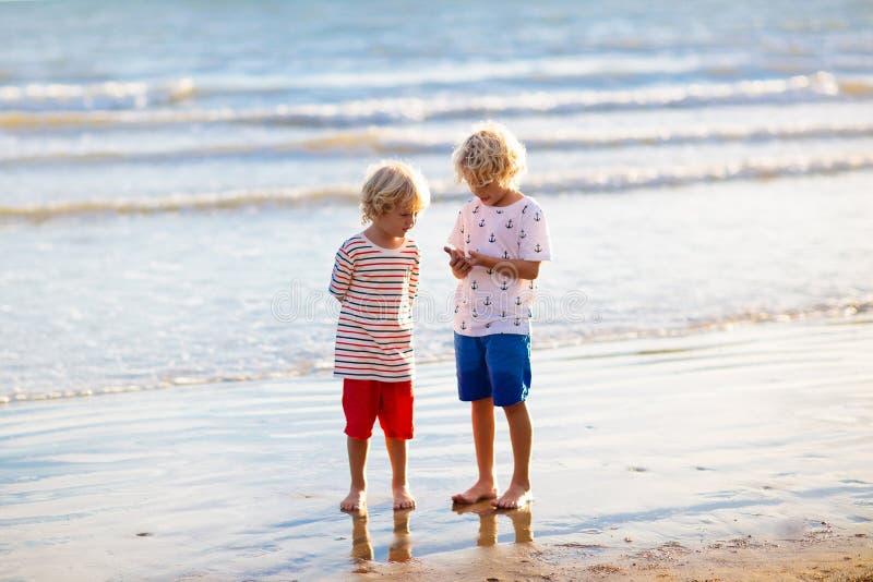 Jonge geitjesspel op tropisch strand Zand en waterstuk speelgoed royalty-vrije stock afbeelding