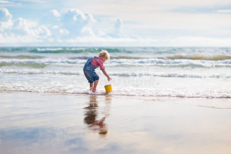 Jonge geitjesspel op tropisch strand Zand en waterstuk speelgoed stock foto's