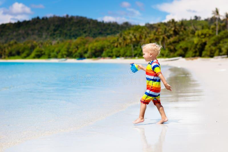 Jonge geitjesspel op tropisch strand Zand en waterstuk speelgoed stock fotografie