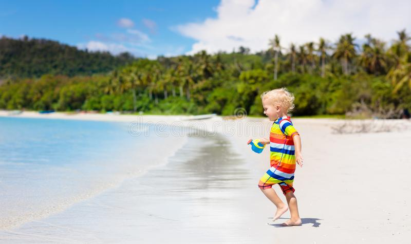 Jonge geitjesspel op tropisch strand Zand en waterstuk speelgoed royalty-vrije stock fotografie