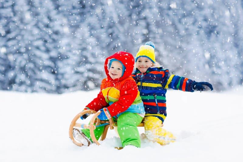 Jonge geitjesspel in sneeuw De rit van de de winterar voor kinderen royalty-vrije stock foto's