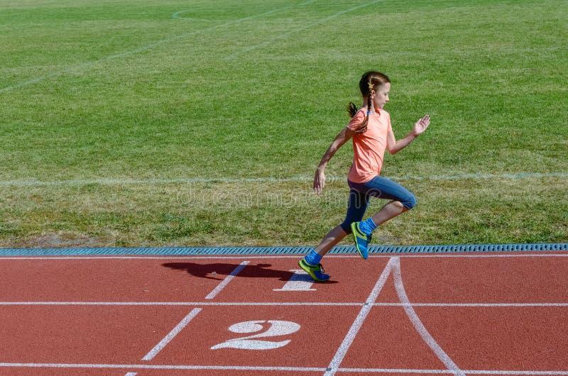 Jonge geitjessport, kind op stadionspoor lopen, opleiding en fitness die stock fotografie