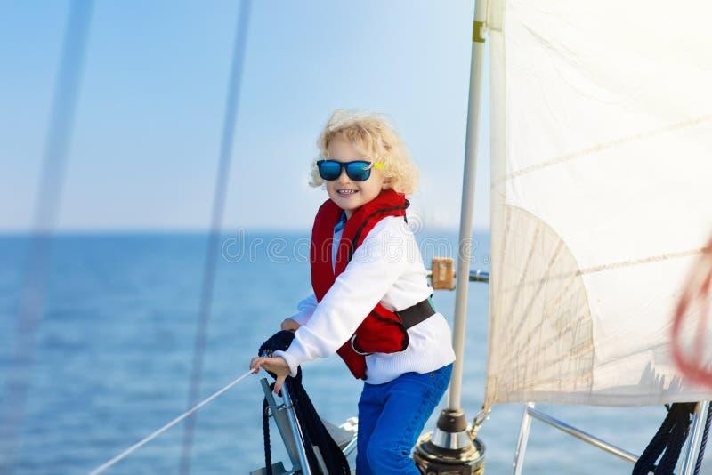 Jonge geitjeszeil op jacht in overzees Kind die op boot varen stock foto's