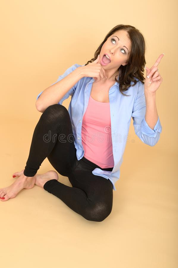 Jonge Gekke Vrouwenzitting op de Vloer die Dwaze Gelaatsuitdrukking trekken stock foto