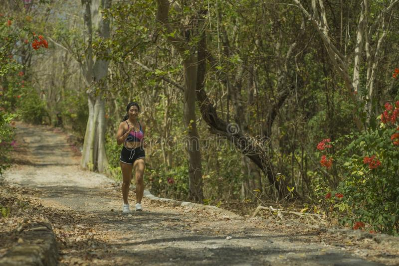 Jonge gelukkige aantrekkelijke en exotische Aziatische Indonesische agentvrouw in joggingtraining in openlucht bij het spooraard  stock afbeelding