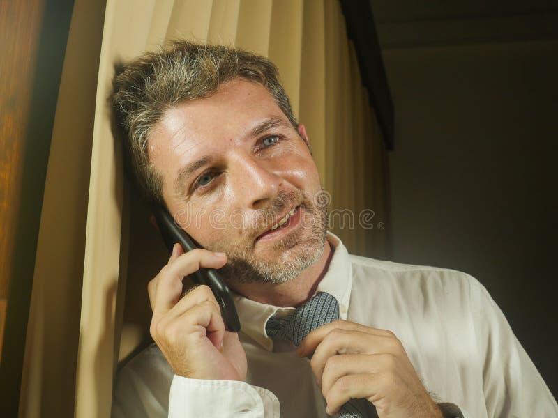 Jonge gelukkige aantrekkelijke en ontspannen zakenman die met het mobiele telefoon vrolijk glimlachen thuis of bureau in succesvo stock afbeelding