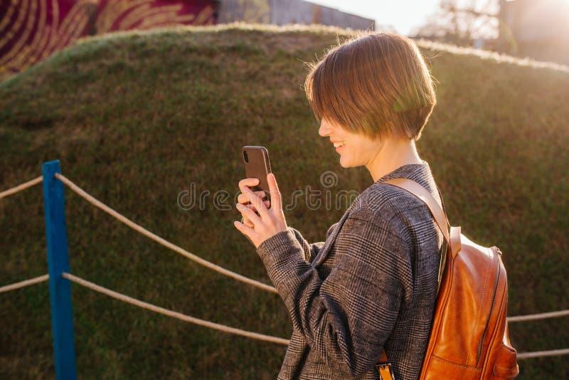 Jonge gelukkige aantrekkelijke kortharige donkerbruine vrouw met telefoon in een park royalty-vrije stock fotografie