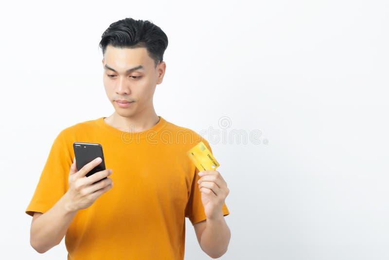 Jonge gelukkige Aziatische man die bericht van smartphone leest en creditcard met copyspace houdt op witte achtergrond royalty-vrije stock fotografie