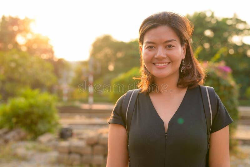 Jonge gelukkige Aziatische toeristenvrouw die backpacker bij het station glimlachen stock foto