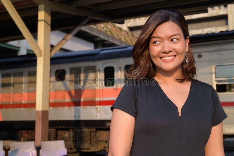 Jonge gelukkige Aziatische toeristenvrouw die bij het station denken stock fotografie