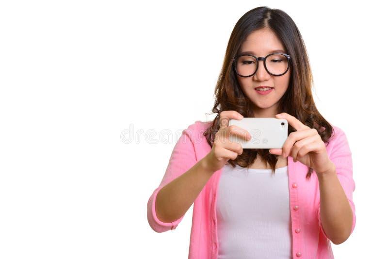 Jonge gelukkige Aziatische vrouw die beeld met mobiele telefoon nemen royalty-vrije stock afbeeldingen