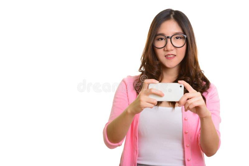 Jonge gelukkige Aziatische vrouw die beeld met mobiele telefoon nemen stock afbeelding