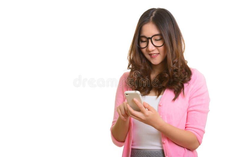 Jonge gelukkige Aziatische vrouw die mobiele telefoon met behulp van royalty-vrije stock foto