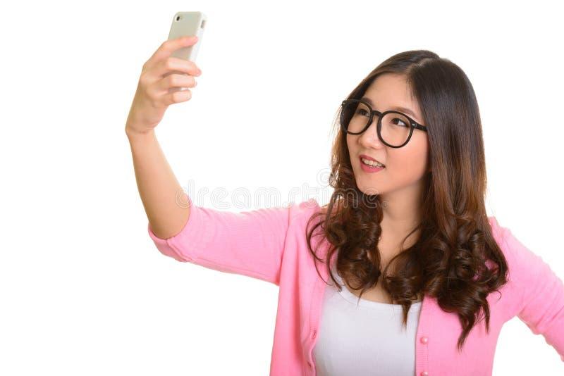 Jonge gelukkige Aziatische vrouw die selfie met mobiele telefoon nemen stock foto