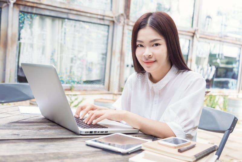 Jonge gelukkige Aziatische vrouw die technologie op haar laptop computer gebruiken stock afbeeldingen
