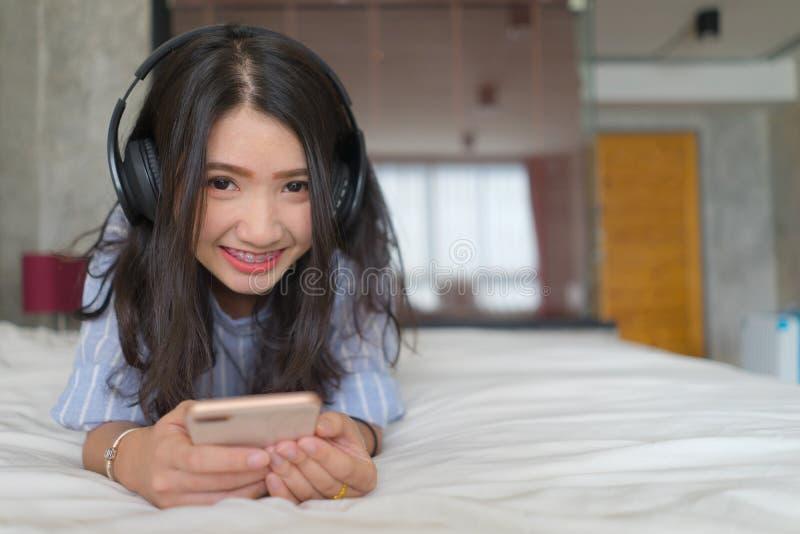 Jonge gelukkige Aziatische vrouw met hoofdtelefoons het luisteren muziek met mobiele telefoon op bed die thuis hebbend pret met I royalty-vrije stock afbeeldingen