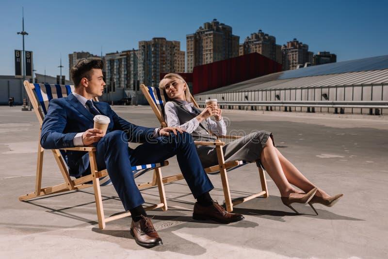 jonge gelukkige bedrijfsmensen die op sunbeds met koffie ontspannen om te gaan royalty-vrije stock foto's