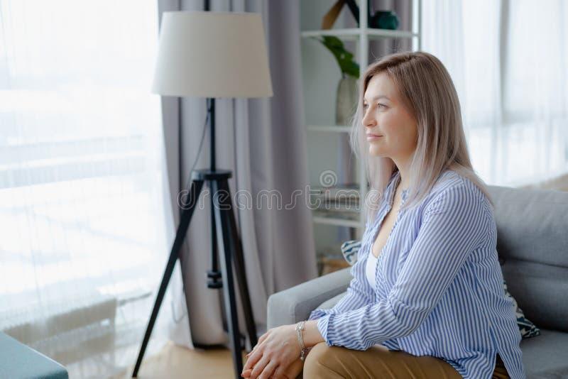 Jonge gelukkige blondevrouw in comfortabel binnenland stock afbeeldingen