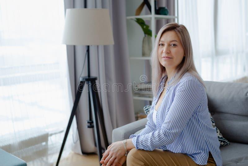 Jonge gelukkige blondevrouw in comfortabel binnenland stock afbeelding