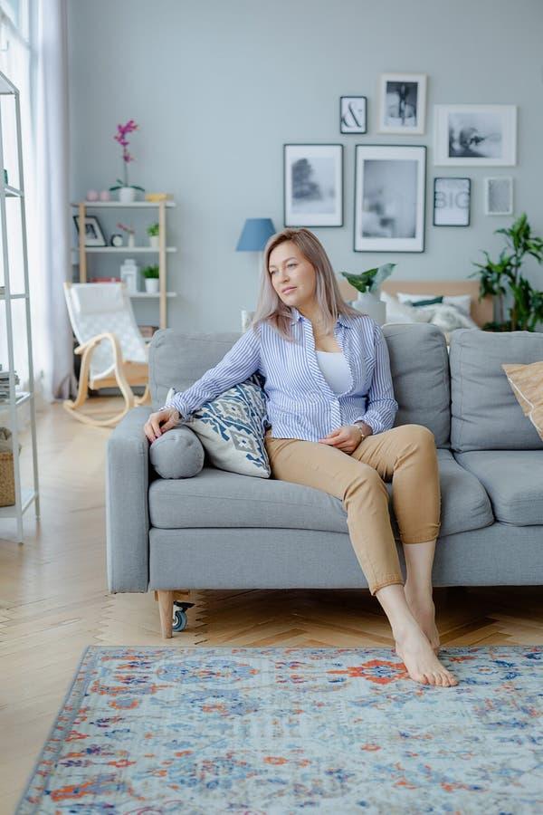 Jonge gelukkige blondevrouw in comfortabel binnenland royalty-vrije stock foto's