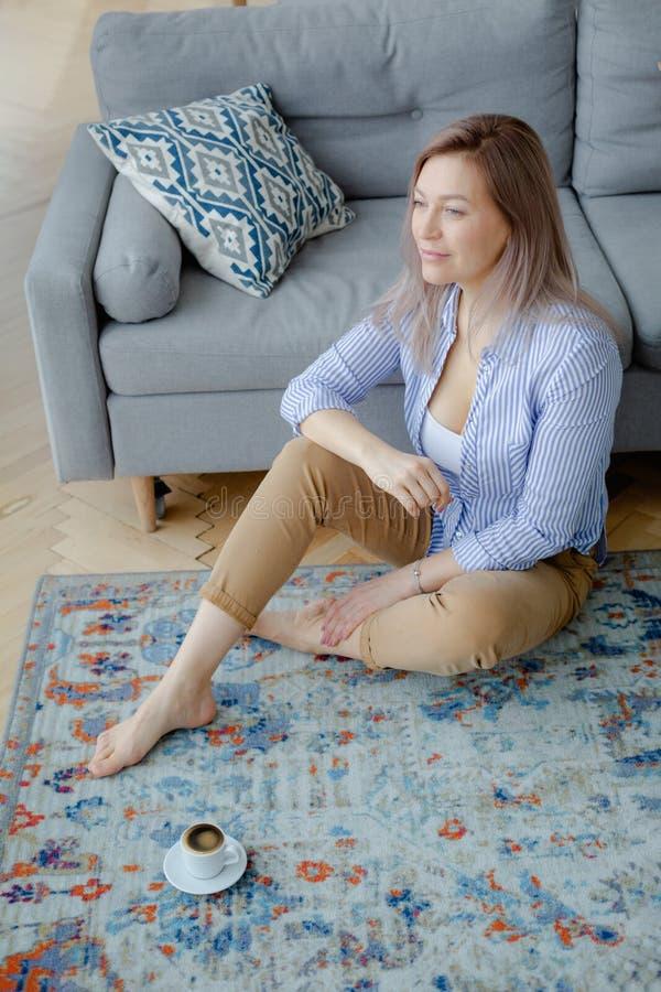 Jonge gelukkige blondevrouw in comfortabel binnenland stock foto's