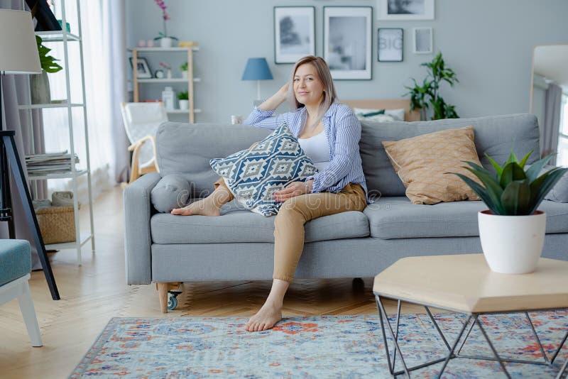 Jonge gelukkige blondevrouw in comfortabel binnenland royalty-vrije stock foto
