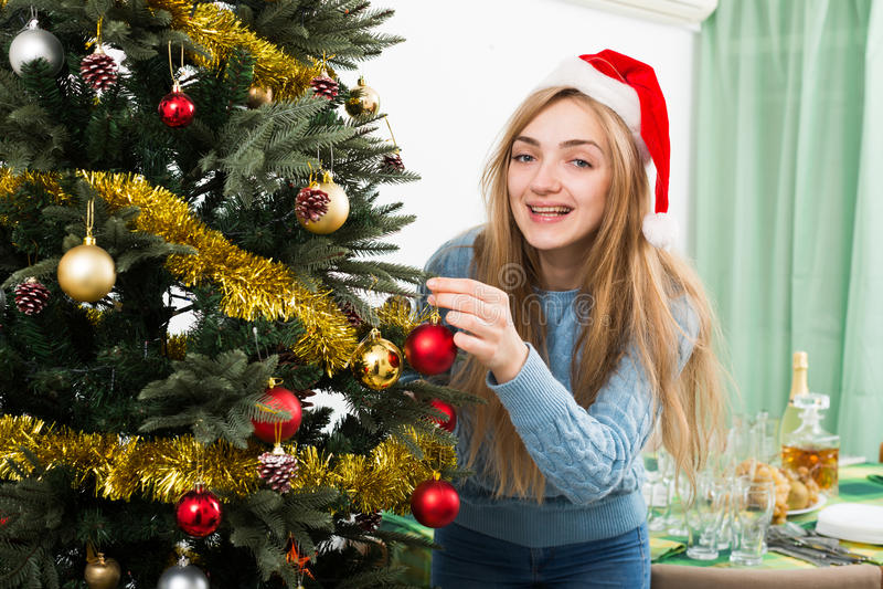 Jonge gelukkige blondie in Kerstmanhoed dichtbij Kerstmisboom royalty-vrije stock afbeelding