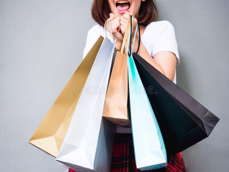 Jonge gelukkige de zomer winkelende Aziatische vrouw met het winkelen zakken op grijze achtergrond stock afbeelding