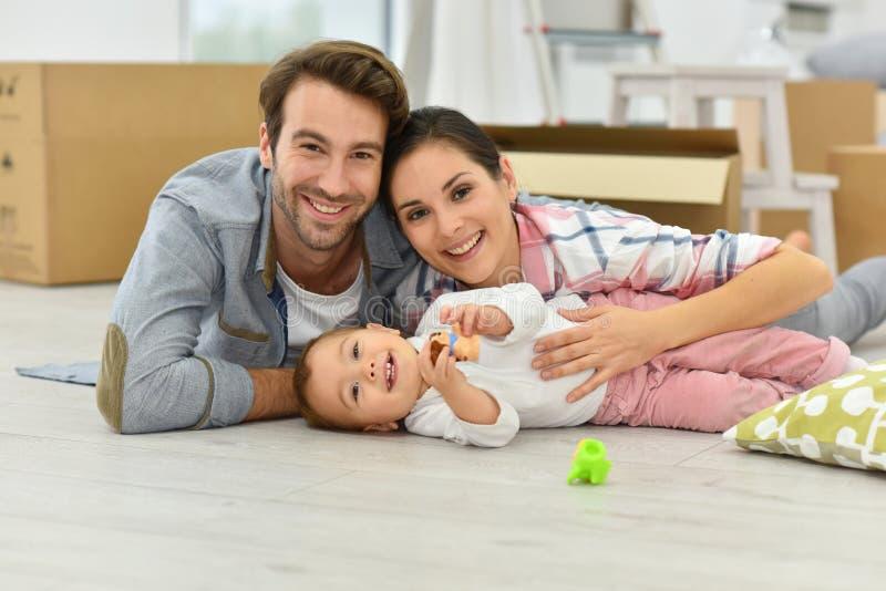 Jonge gelukkige die familie onlangs in nieuw huis wordt bewogen stock fotografie