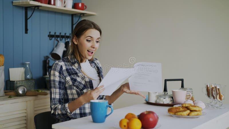 Jonge gelukkige die vrouw wordt verrast om goed nieuws te ontvangen die brief in de keuken lezen terwijl ontbijt thuis vroeg hebb stock foto