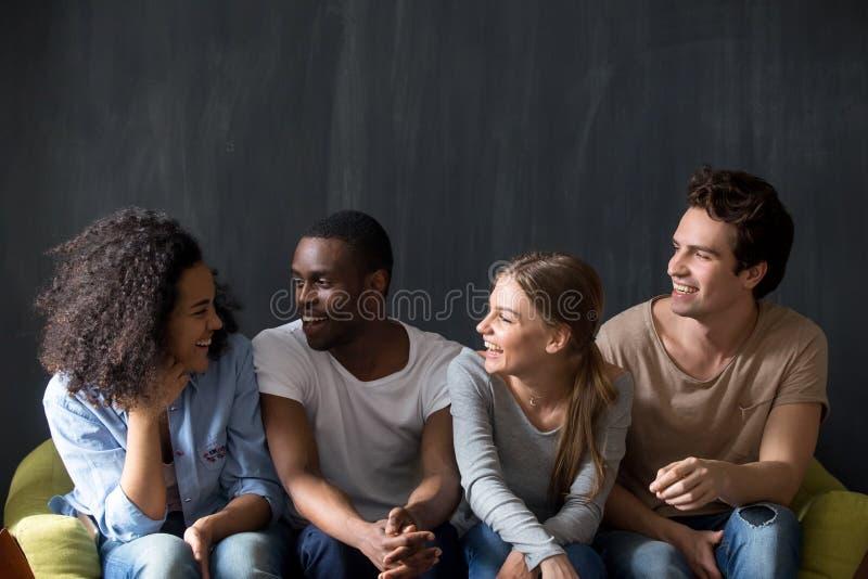 Jonge gelukkige diverse vrienden die aan biracial het glimlachen meisjesgrap luisteren royalty-vrije stock fotografie