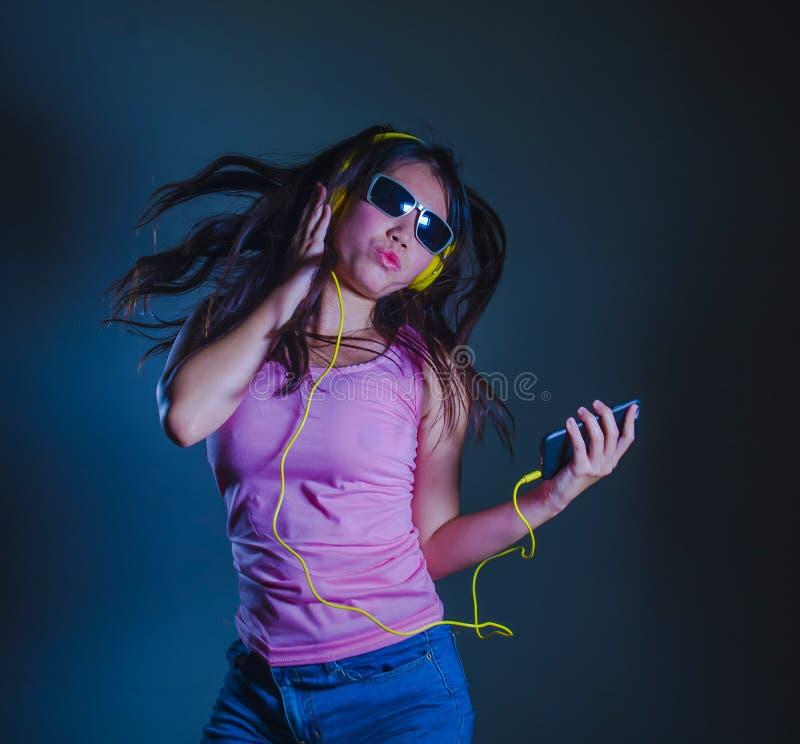 Jonge gelukkige en aantrekkelijke Aziatische Koreaanse vrouw die en aan het lied dansen zingen die aan muziek die met gele hoofdt royalty-vrije stock foto's