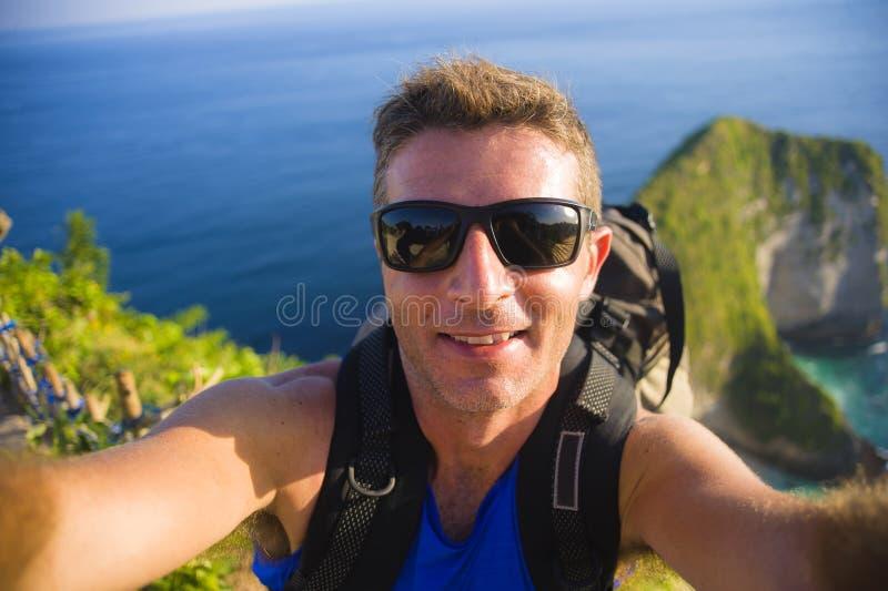 Jonge gelukkige en aantrekkelijke backpackermens die selfie portretfoto met mobiele telefoon voor het verbazende overzeese landsc stock foto's