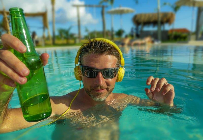 Jonge gelukkige en aantrekkelijke mens die aan muziek met hoofdtelefoon bij het tropische toevlucht zwembad het drinken bier toeg royalty-vrije stock foto's