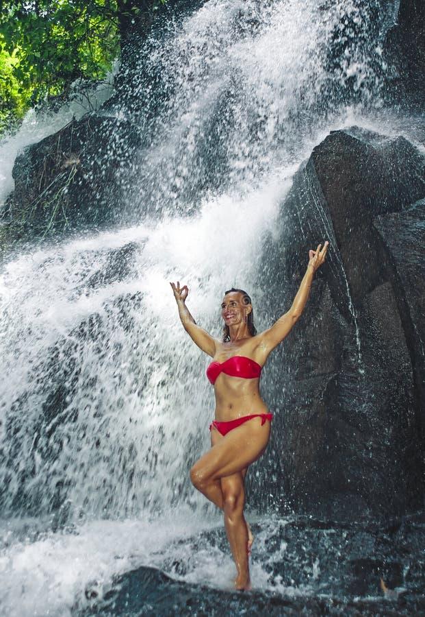 Jonge gelukkige en aantrekkelijke vrouw die yogaoefening doen die zich onder mooie tropische waterval bevinden die het natte glim royalty-vrije stock afbeeldingen