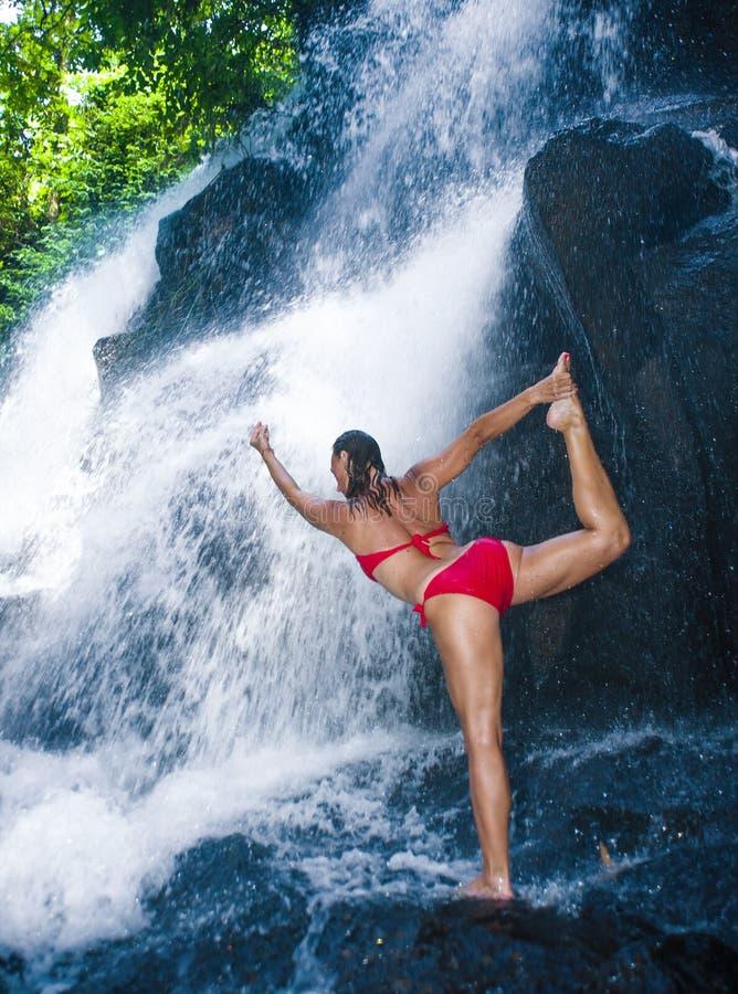 Jonge gelukkige en aantrekkelijke vrouw die yogaoefening het stellen doen onder mooie tropische waterval die het natte glimlachen stock afbeeldingen