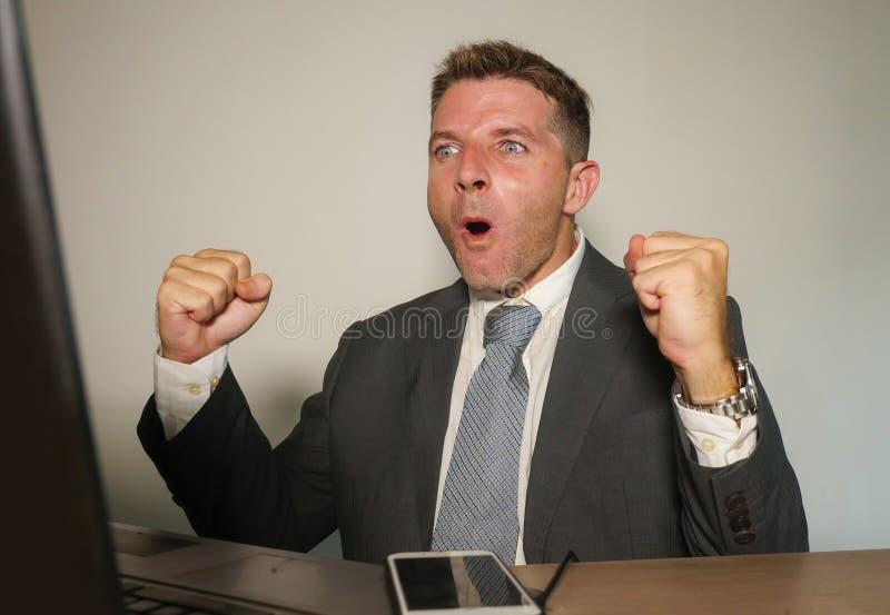 Jonge gelukkige en aantrekkelijke zakenman die bij het bureau van de bureaucomputer het vieren succes binnen opgewekt en vrolijk  stock foto