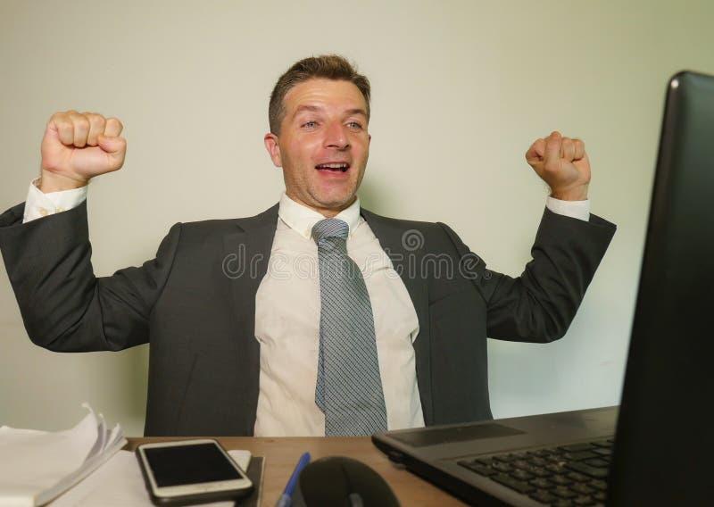 Jonge gelukkige en aantrekkelijke zakenman die bij het bureau van de bureaucomputer het vieren succes binnen opgewekt en vrolijk  royalty-vrije stock afbeeldingen