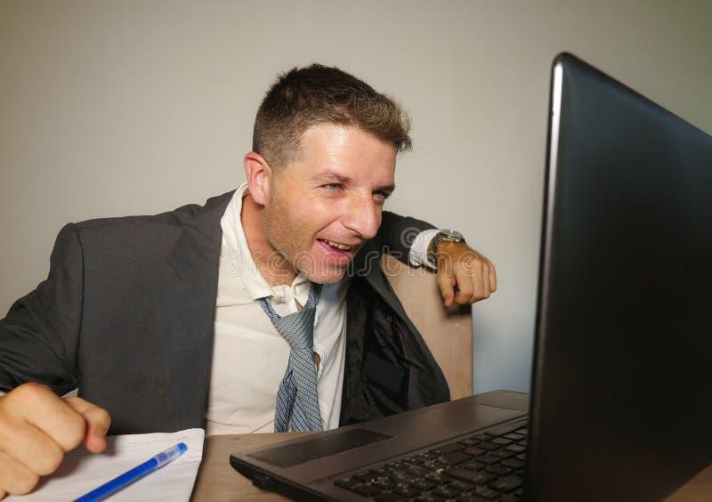 Jonge gelukkige en aantrekkelijke zakenman die bij het bureau van de bureaucomputer het vieren succes binnen opgewekt en vrolijk  royalty-vrije stock afbeelding