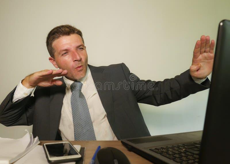 Jonge gelukkige en aantrekkelijke zakenman die bij het bureau van de bureaucomputer het vieren succes binnen opgewekt en vrolijk  stock afbeelding