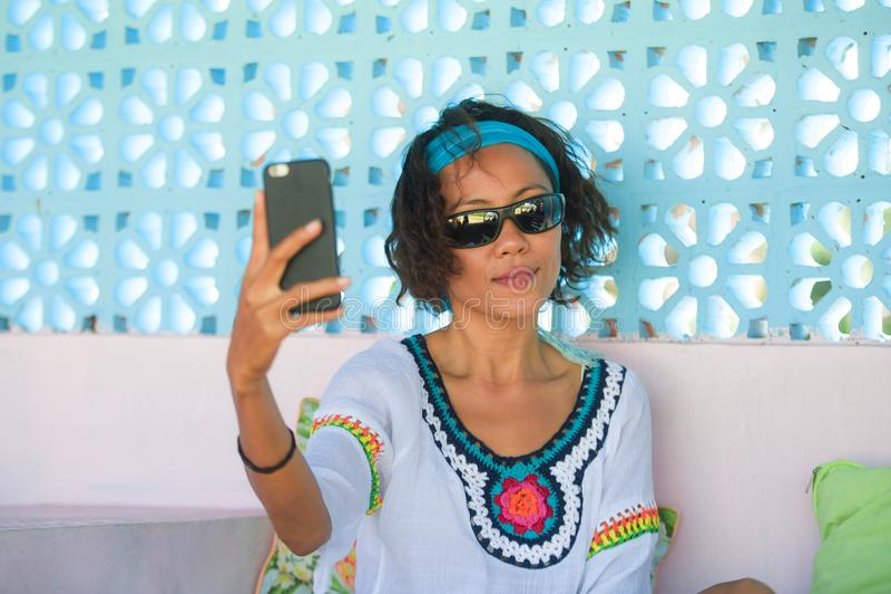 Jonge gelukkige en aantrekkelijke Zuidoostaziatische Thaise vrouw die selfie fotoportret met het mobiele telefooncamera vrolijk s royalty-vrije stock afbeelding