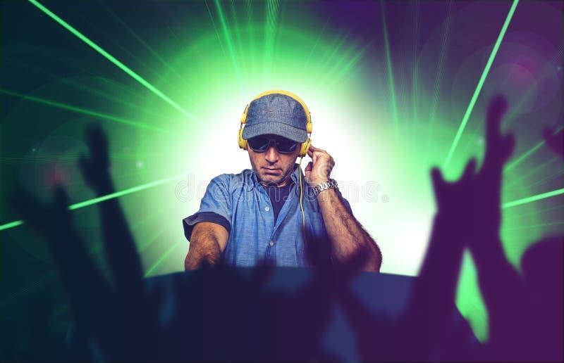 Jonge gelukkige en koele deejay speelmuziek bij partijgebeurtenis in nachtclub die technoliederen op laser en flitslichtenachterg stock foto