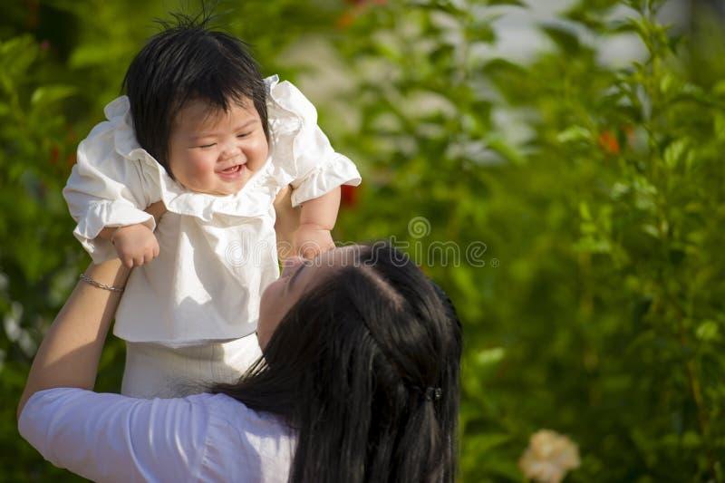 Jonge gelukkige en leuke Aziatische Chinese vrouw die en met haar dochter genieten van spelen die van het babymeisje haar houden  stock afbeelding